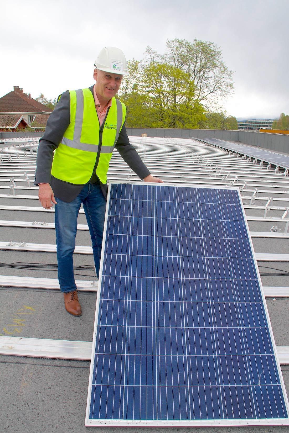 SOLENERGI-LAGRING: Brynjar Henriksen viser fram solcellepanelene som nå monteres på taket av den nye skolen.
